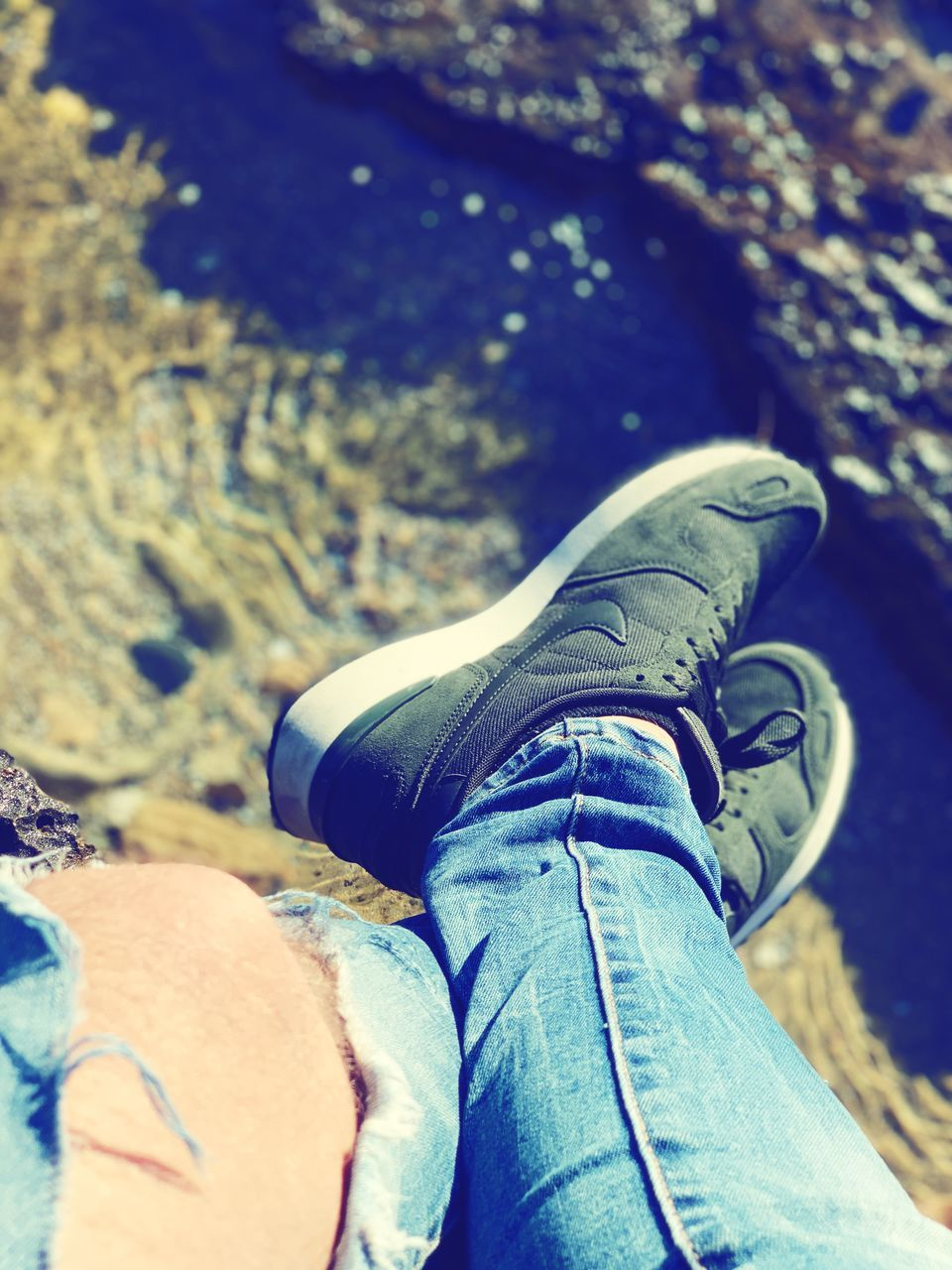 low section, body part, shoe, human body part, one person, human leg, personal perspective, real people, jeans, lifestyles, day, leisure activity, casual clothing, close-up, men, high angle view, focus on foreground, rock - object, rock, human limb, human foot, outdoors