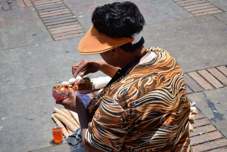 High angle view of man eating hot dog on footpath