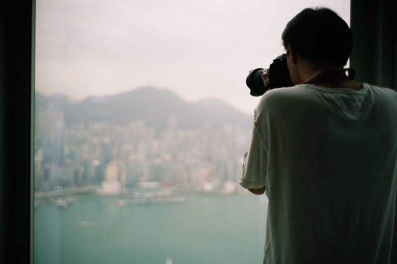 Rear view of man photographing cityscape against sky