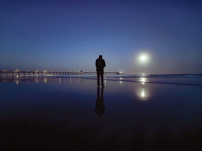 Rear view of man standing at beach during dusk