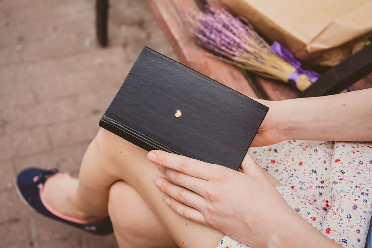 Low section of woman sitting on book