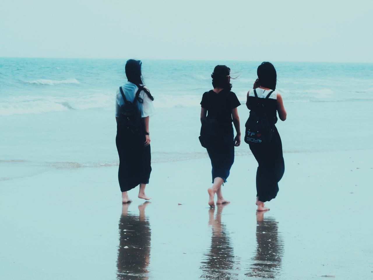 Full Length Rear View Of Friends Walking At Beach Against Clear Sky