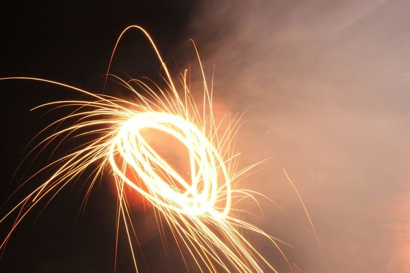 Low angle view of illuminated wire wool against sky at night