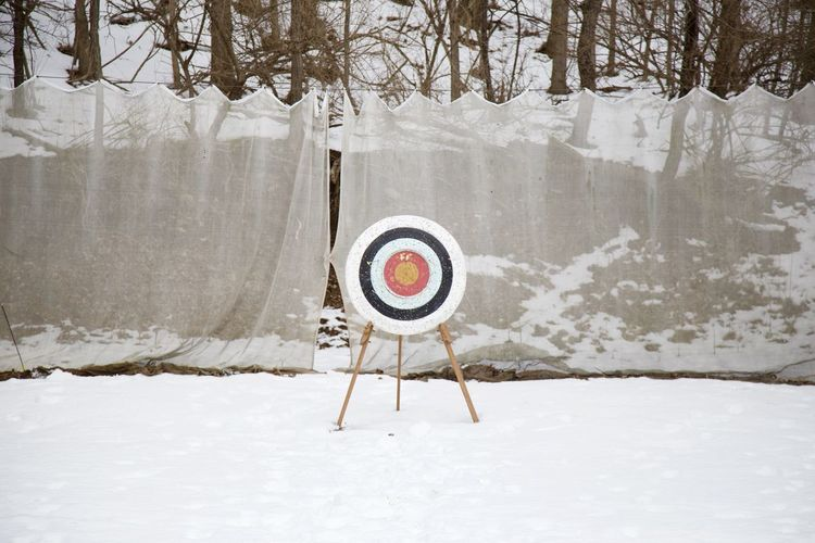 Dartboard On Snow Covered Field