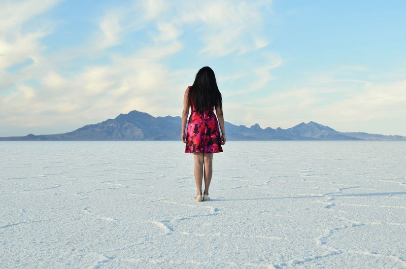 Rear view of woman standing on salt flat against sky