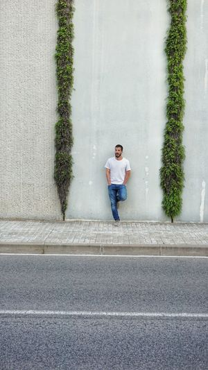 Man cycling on road against wall