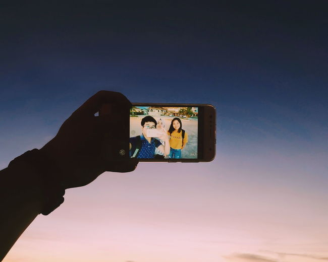 Low angle view of hand holding smart phone against sky