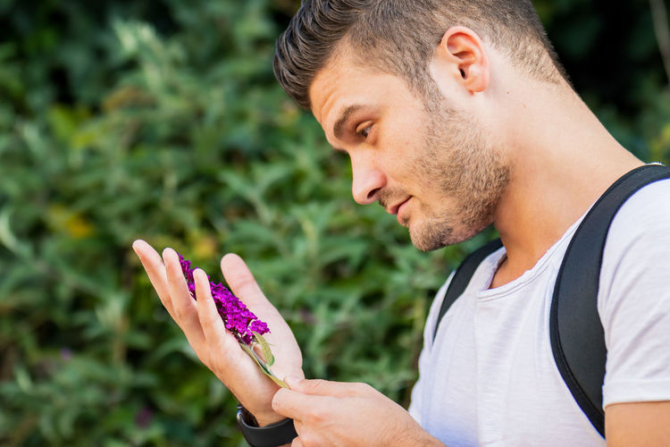 Close-up portrait of young man holding purple flower