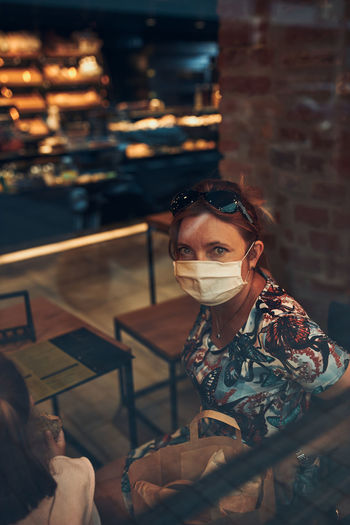 Portrait of woman wearing mask sitting at cafe