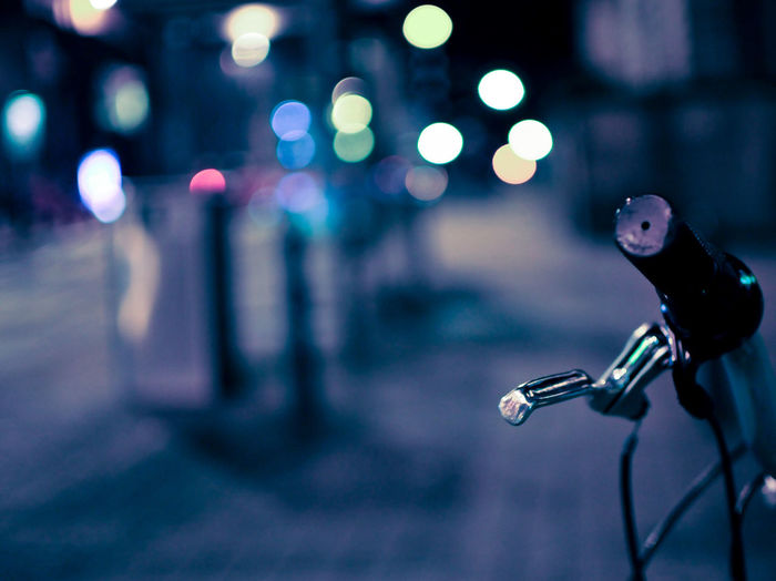 Close-up of bicycle on illuminated city street at night