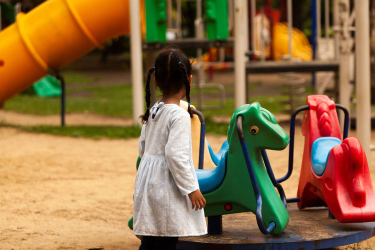 Side view of cute girl playing at playground