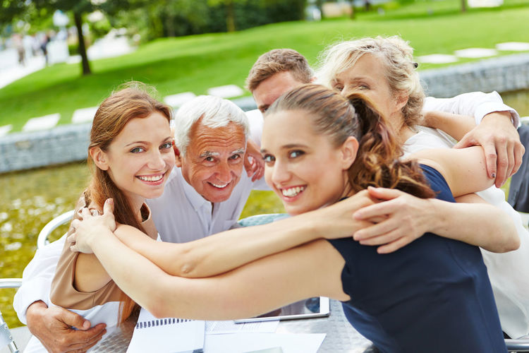 Cheerful Business Colleagues With Arms Around Sitting At Table