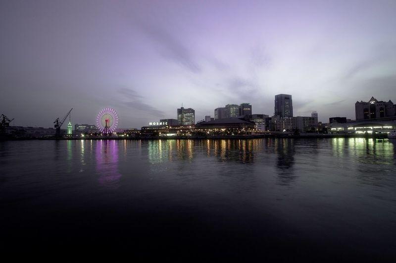 City Skyline And Illuminated Ferris Wheel By River Against Sky At Dusk