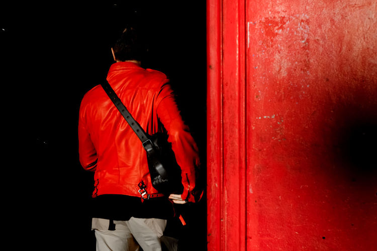 Rear view of man next to red phone booth
