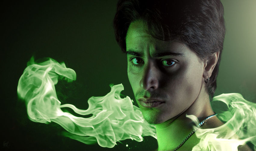 Close-up portrait of man with flame against colored background