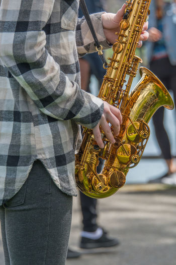 Midsection Of Street Musician Playing Saxophone