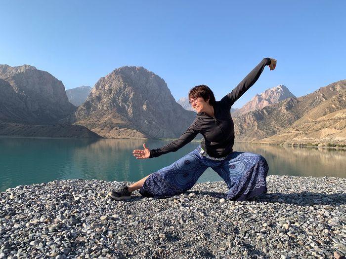 Full length of man sitting on rock by lake