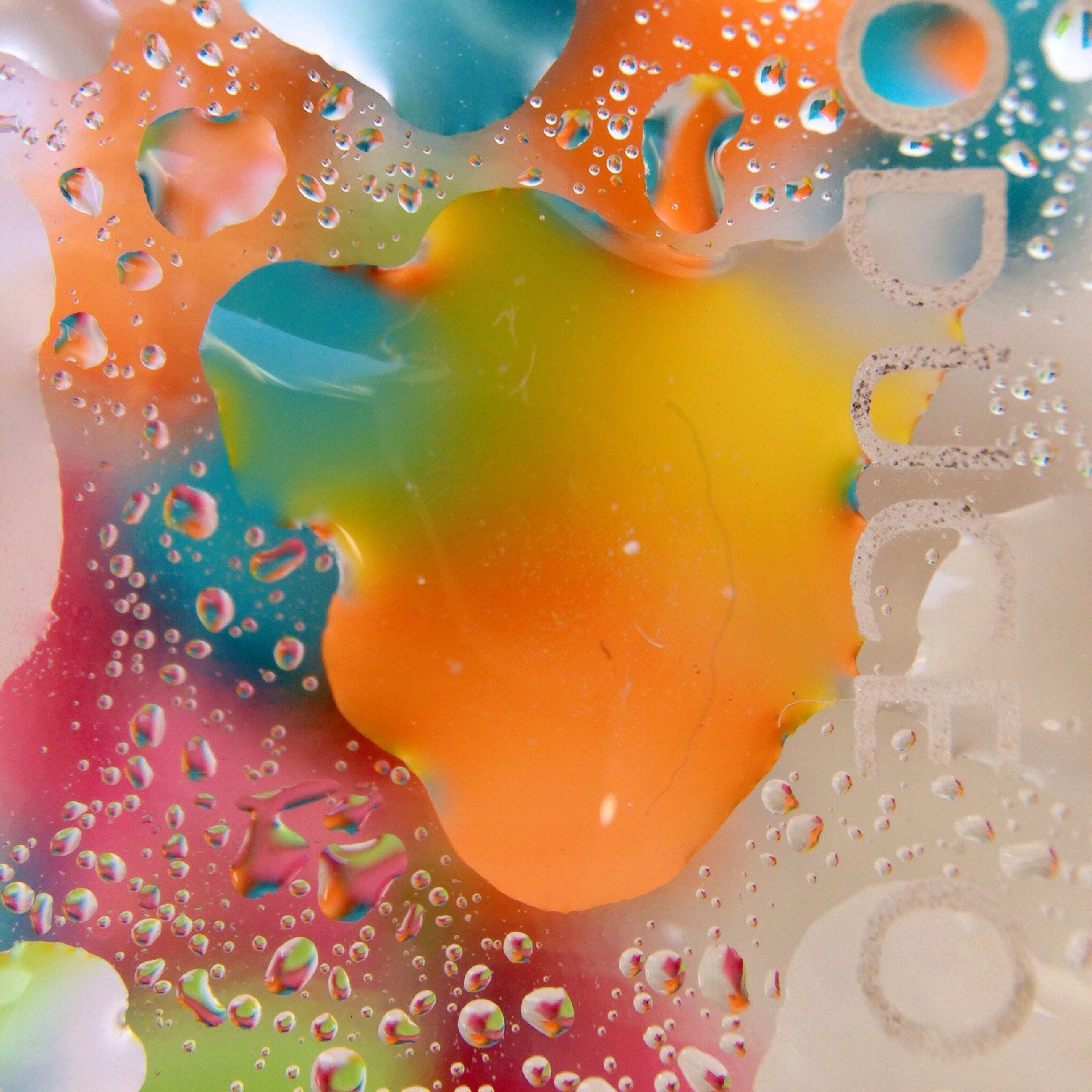 water, indoors, close-up, drop, wet, transparent, pattern, high angle view, bubble, red, multi colored, orange color, glass - material, reflection, freshness, no people, creativity, detail, shape, design