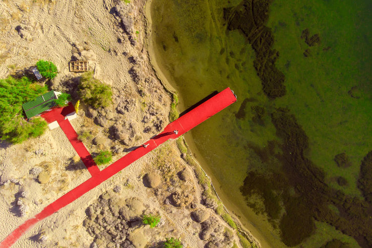 Aeiral view of red pier on the beach. High Angle View Day Nature No People Water Land Green Color Outdoors Red Transportation Plant Dirt Tranquility Beauty In Nature Scenics - Nature Sand Pipeline Non-urban Scene Mode Of Transportation Real People Plant Dronephotography Top View Aerial View Green