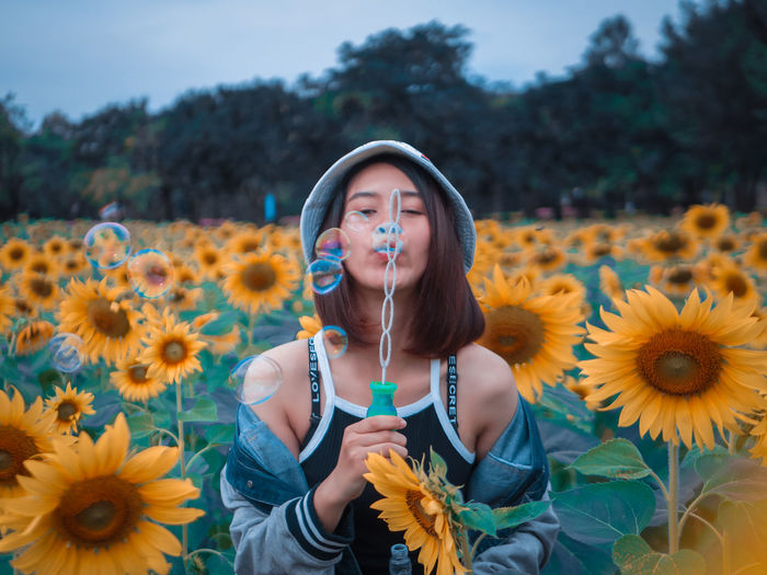 Young woman blowing bubbles amidst flowering sunflowers