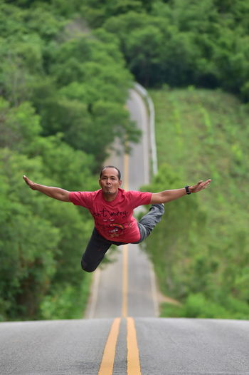 Man with arms outstretched levitating over road