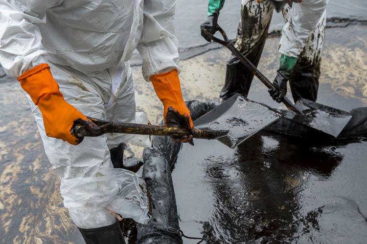 Midsection Of Manual Worker Cleaning Crude Oil At Beach