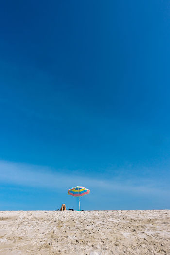 Parasol at beach against blue sky