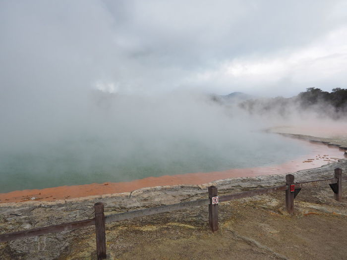 Scenic View Of Geothermal Lake Against Cloudy Sky