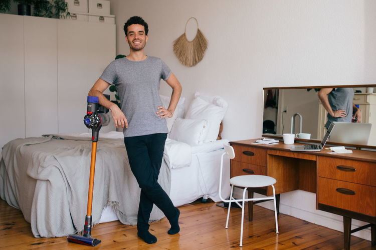 Full length of man standing on table at home