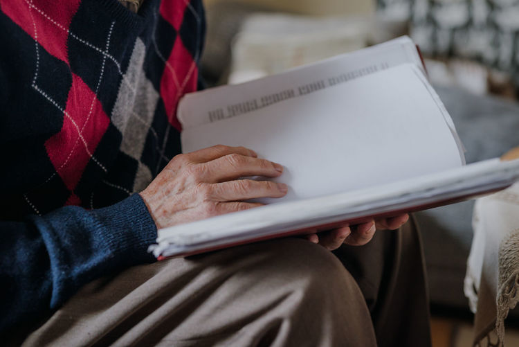 Midsection of senior woman reading book in home