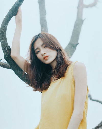Adult Arms Raised Beautiful Woman Beauty Brown Hair Casual Clothing Contemplation Front View Hair Hairstyle Lifestyles Long Hair Looking At Camera One Person Portrait Real People Standing Teenager Waist Up Women Young Adult Young Women