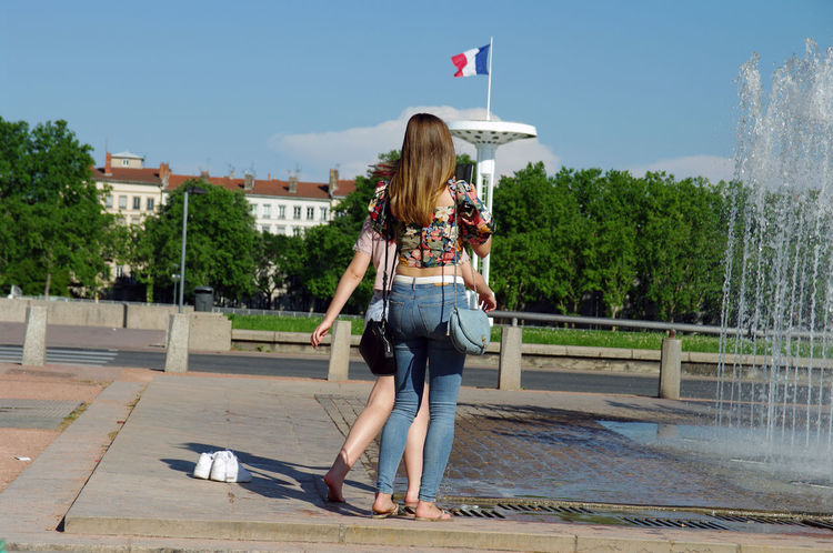 Building Exterior Casual Clothing Day Flag Full Length Leisure Activity Lifestyles Lyon Motion One Person One Young Woman Only Outdoors Patriotism People Playing Real People Sky Standing Taking Pictures Tree Water Water Jet Women Young Adult Young Women