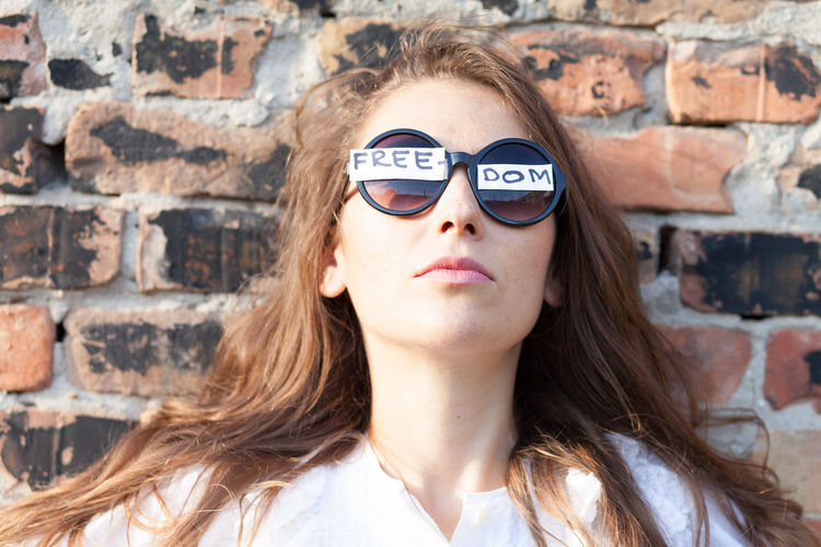 Woman Wearing Sunglasses With Freedom Text Against Brick Wall