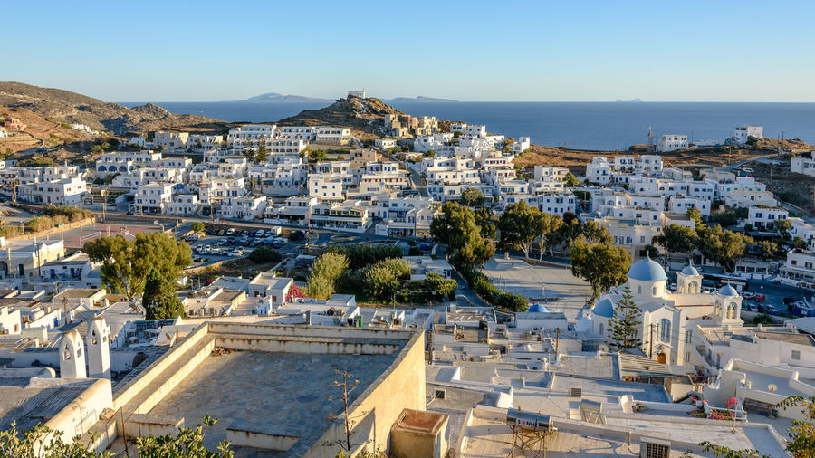 High angle view of townscape by sea against clear sky