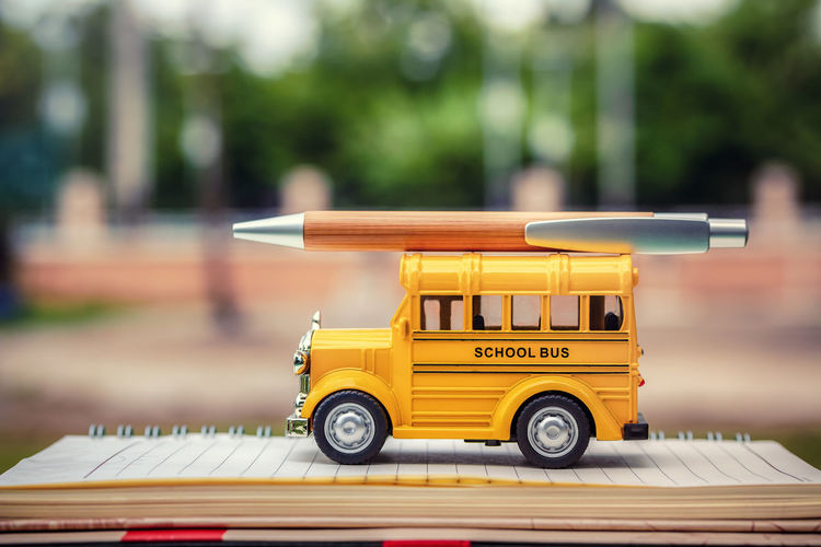 Close-up of book pen and toy bus