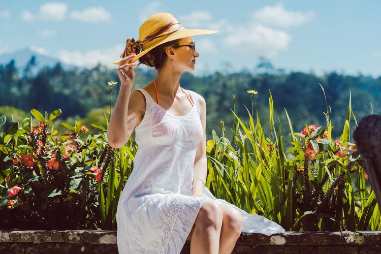 Woman wearing hat against plants