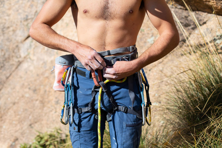 Close up of climber making a knot called double eight with the rope in the harness Knot Double Eight Harness Climbing Climber Rope Close Up Protection Rock Safety Mountaineering Security Connect Effort Nature Outdoors Lifestyle Accesory Equipment Sport Mountain Adventure Secure Wearing Team
