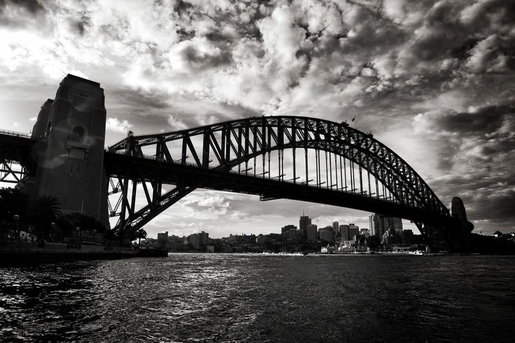 Low angle view of sydney harbor bridge against cloudy sky