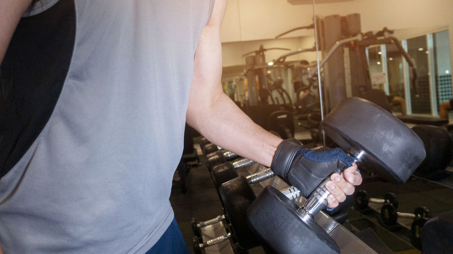 Midsection of man holding dumbbell in gym