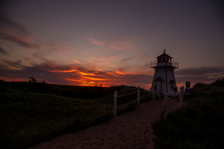 Lighthouse amidst buildings against sky during sunset
