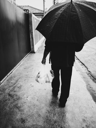 Rear view of man with umbrella walking on footpath