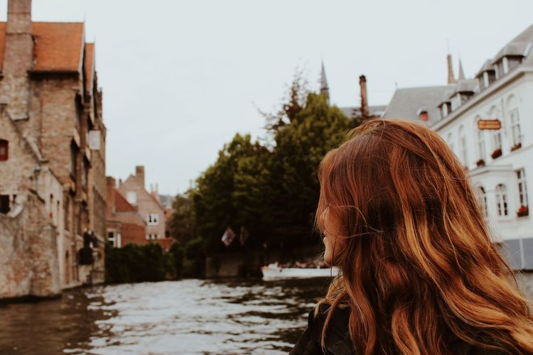Woman looking away while sitting in boat on canal