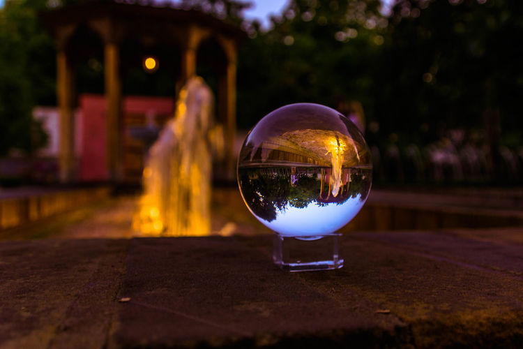 Reflection of illuminated crystal ball on glass against trees at night