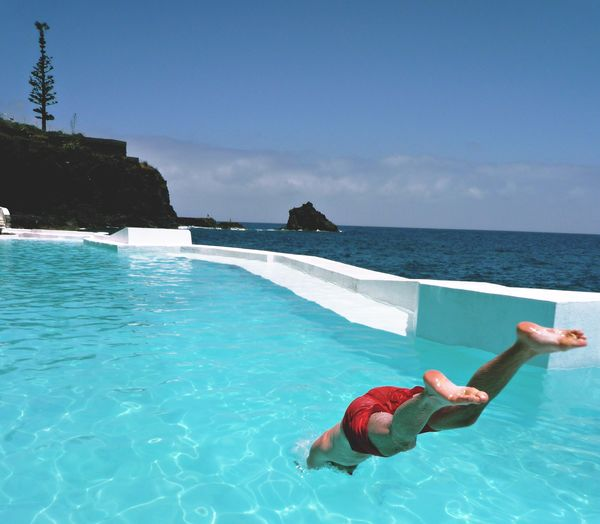 High angle view of man diving in swimming pool against blue sky