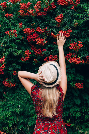 Midsection of woman with red flowers in park