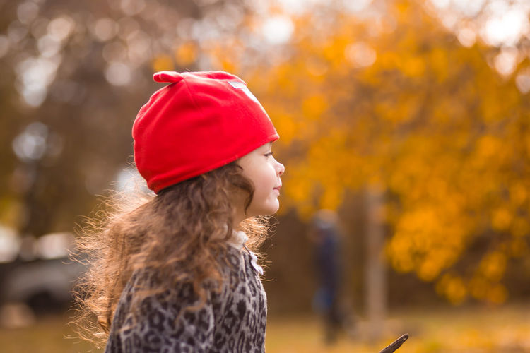 Close-up of girl with autumn leaves