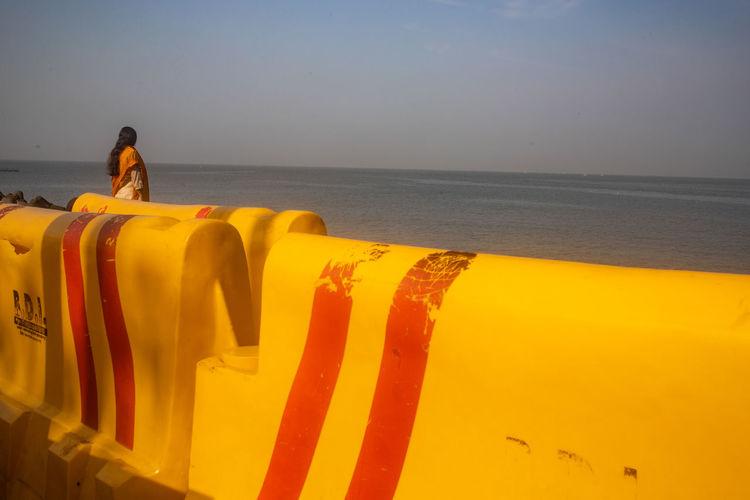 Yellow umbrella on beach against sky