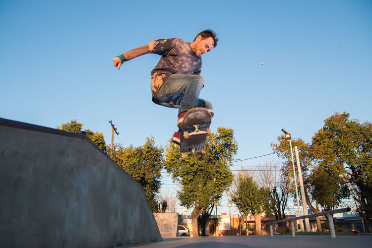 Low angle view of man skateboarding against clear sky