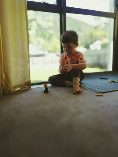 Boy playing with toy by glass window at home