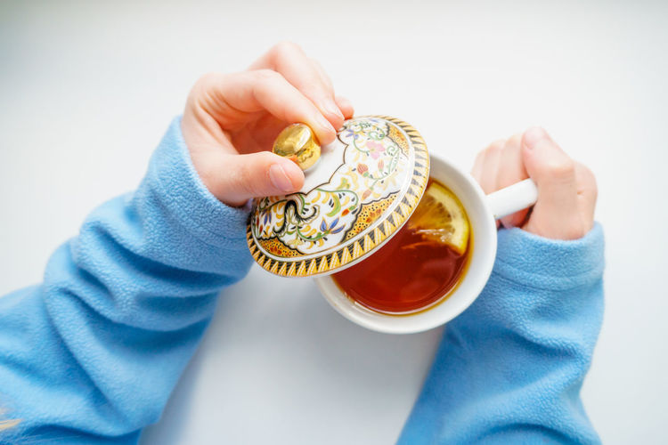 Cropped person holding tea cup on white background